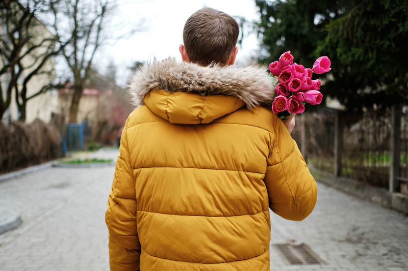 Rear view of woman standing by yellow flower in city