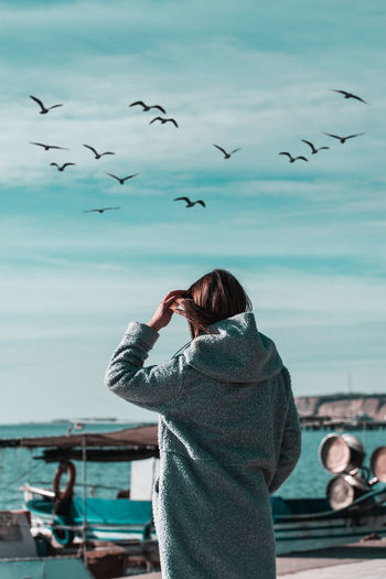Rear view of woman with seagulls flying over sea