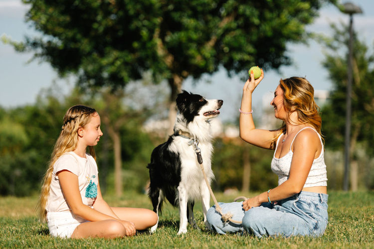 Rear view of woman with dog sitting on field