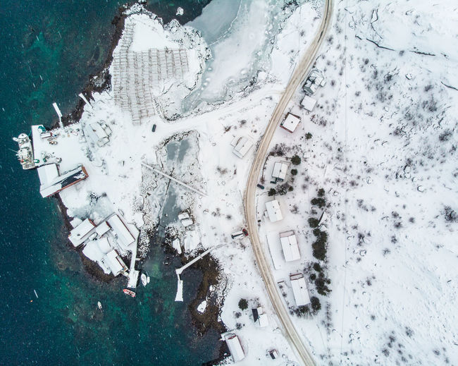 Aerial view of snowy houses by sea in town