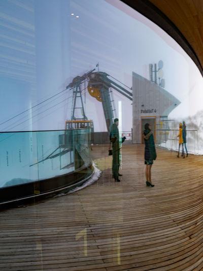 People walking on boat in city against sky