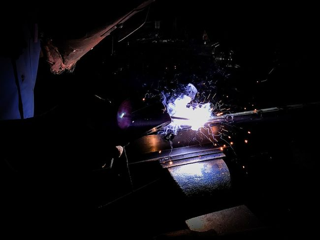 Sparks and smoke Caused by welding in production process Close-up Factory Flame Glowing Heat - Temperature Illuminated Indoors  Industry Manual Worker Men Metal Industry Night Occupation Occupational Safety And Health One Person People Real People Skill  Sparks Steel Worker Welder Welding Work Tool Working Workshop