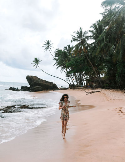 Beach Land Sea Water Tree Tropical Climate Palm Tree Real People One Person Lifestyles Sky Leisure Activity Sand Standing Full Length Nature Young Women Outdoors Sri Lanka Running Walking Girl Dress Summer Rock