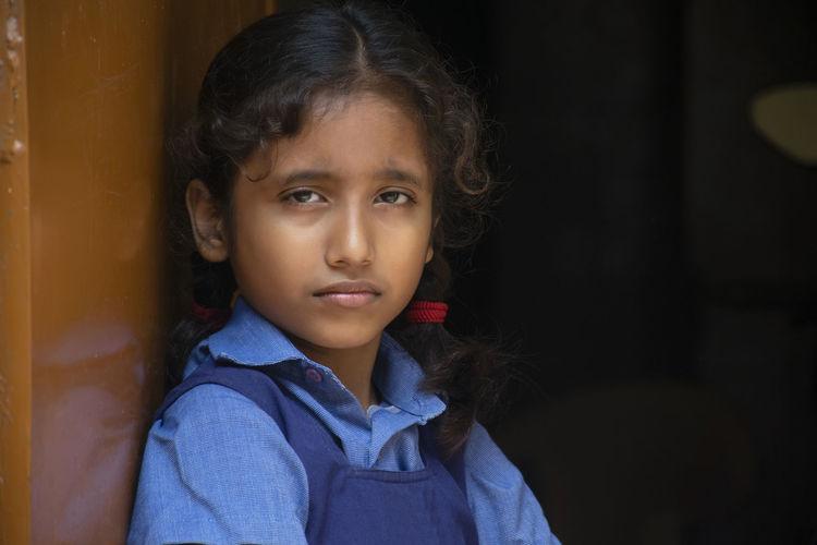 Portrait of girl wearing school uniform standing by door