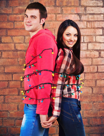 Portrait of smiling young couple standing against brick wall