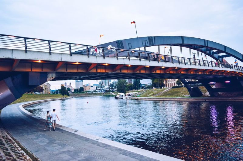 Walking couple Water Bridge Architecture Connection Transportation Built Structure Sky Bridge - Man Made Structure Reflection Wet Nature Day Incidental People City Men River Real People Group Of People Building Exterior Outdoors