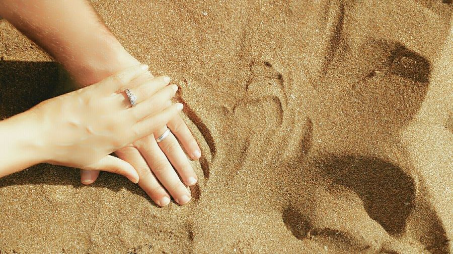 Cropped Image Of Hands With Wedding Rings On Sand