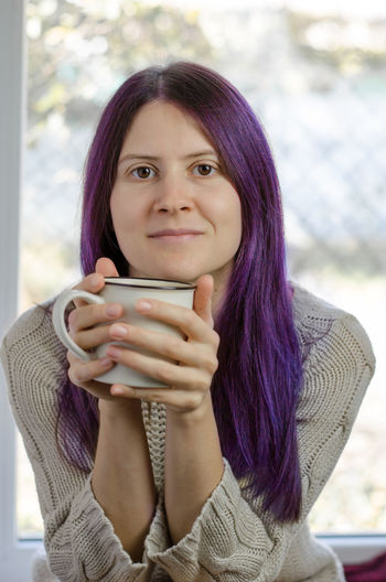 Portrait of a beautiful young woman drinking coffee