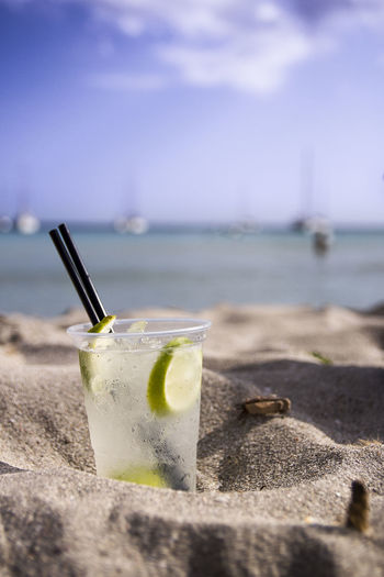 High angle view of drink on table at beach against sky
