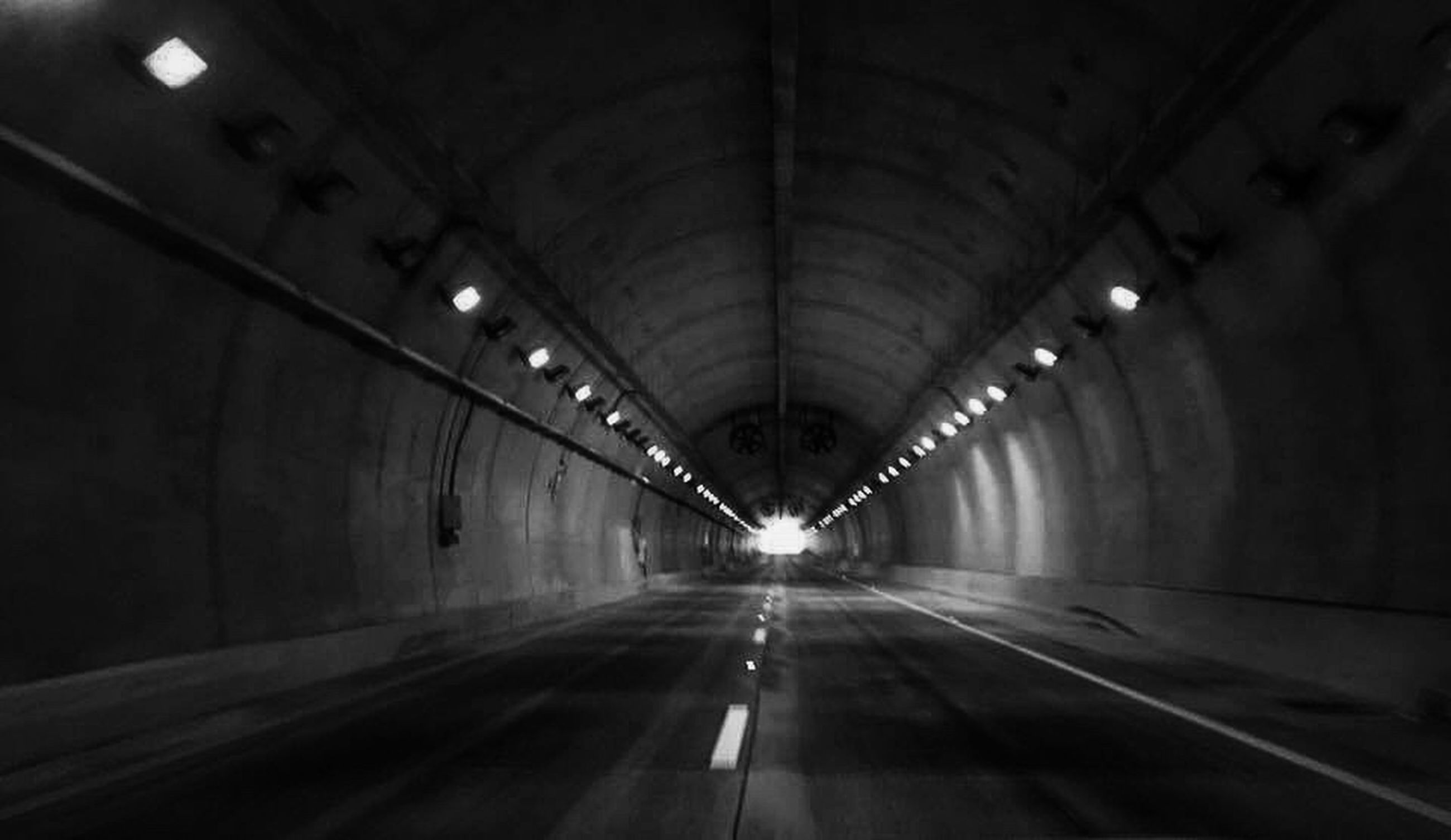 indoors, the way forward, illuminated, tunnel, diminishing perspective, ceiling, transportation, vanishing point, lighting equipment, empty, built structure, architecture, night, arch, light - natural phenomenon, long, corridor, road, interior, light at the end of the tunnel