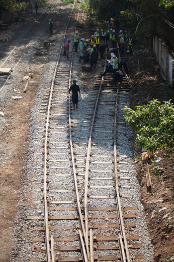 High angle view of people walking on railroad tracks