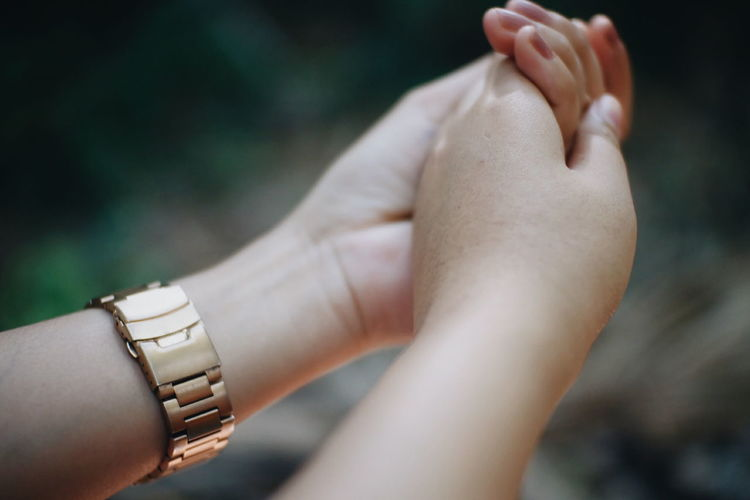 Cropped image of women holding hands outdoors