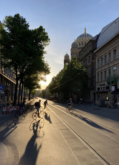 People riding bicycle on street amidst buildings in city