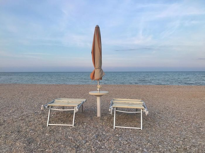 2 beach chairs and a closed umbrella at the beach in the evening Travel Photography Beach Umbrella Closed Sky Horizon Over Water Horizon Sea Water Beach Chair Tranquil Scene Beauty In Nature Scenics - Nature Absence Outdoors No People Sand Seat Tranquility My Best Travel Photo The Traveler - 2019 EyeEm Awards The Mobile Photographer - 2019 EyeEm Awards