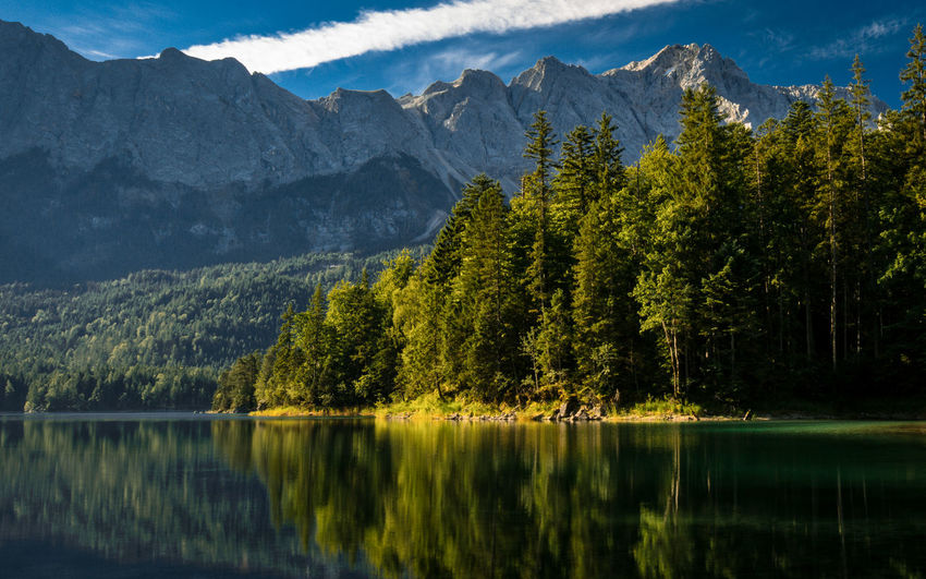 Scenic view of lake by trees and mountains against sky