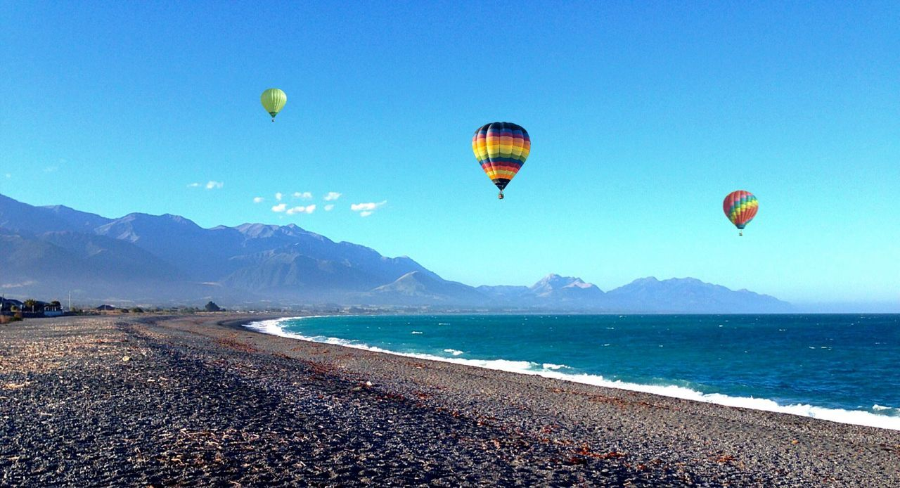 sea, mountain, scenics, nature, beauty in nature, day, flying, clear sky, outdoors, sky, blue, mid-air, water, hot air balloon, multi colored, adventure, mountain range, parachute, ballooning festival, no people