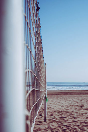 Close-up of volleyball net against sea at beach