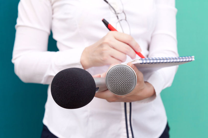 Female journalist taking notes, holding two microphones at a press conference. Public relations-PR Censorship Freedom Journalist Mic PR Press Reporting Audio Equipment Broadcasting Close-up Correspondent Female Hands Writing Information Input Device Journalism Media Conference Microphone News News Event Notebook Pen Pencil And Notebook Press Conference Unrecognizable Person Writing