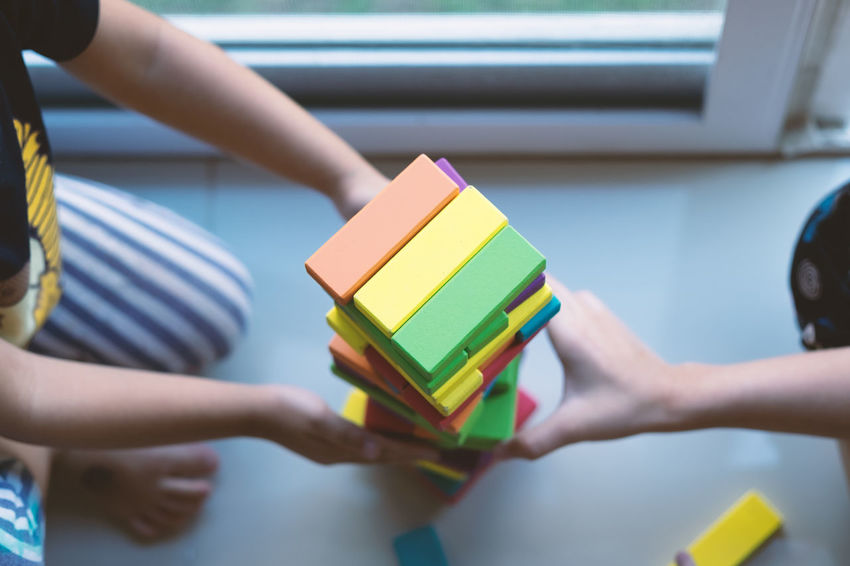 Hand Real People Holding Indoors  Multi Colored Two People People Focus On Foreground Lifestyles Leisure Activity Childhood Togetherness Finger Unrecognizable Person Midsection High Angle View Top View Kids Girls Children Home Teamwork Sisterhood Building Wooden Blocks