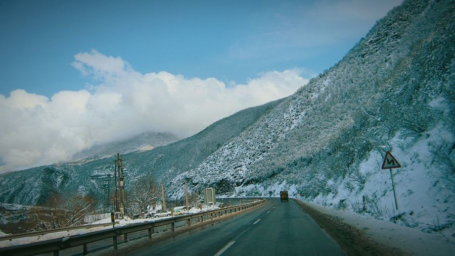 Road along snowcapped mountains against sky