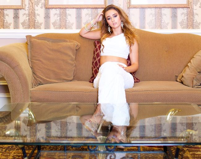 Portrait of beautiful young woman sitting on sofa at home