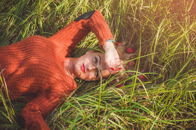 Woman laying on green grass with loose hair with apples Nature Portrait Relaxation Day Field Outdoors Grass Beautiful Woman Contemplation Plant Land Growth Adult Lying Down Lifestyles Young Adult Green Color Lying On Back One Person Casual Clothing Leisure Activity Real People Women