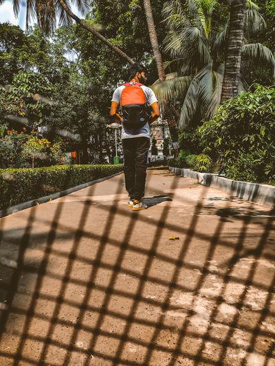 Full length rear view of man walking on sidewalk
