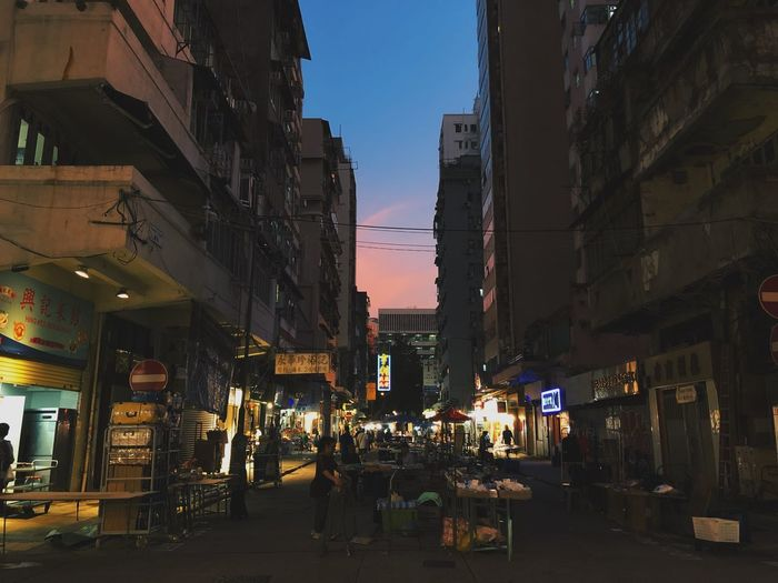 People walking on illuminated street amidst buildings in city at dusk