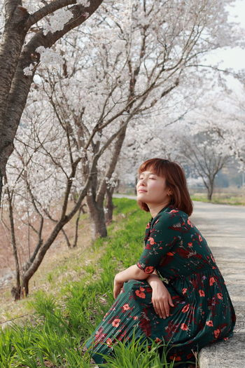 Side view of woman sitting on footpath against cherry trees at park
