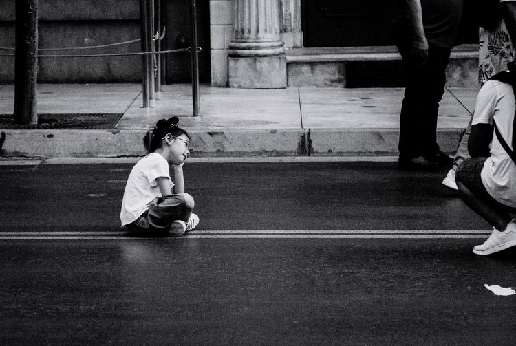 Side View Of Girl Sitting On Road In City