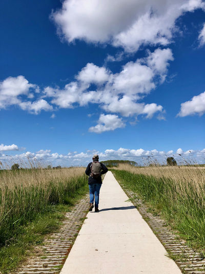 Rear view of man walking on road amidst field against sky