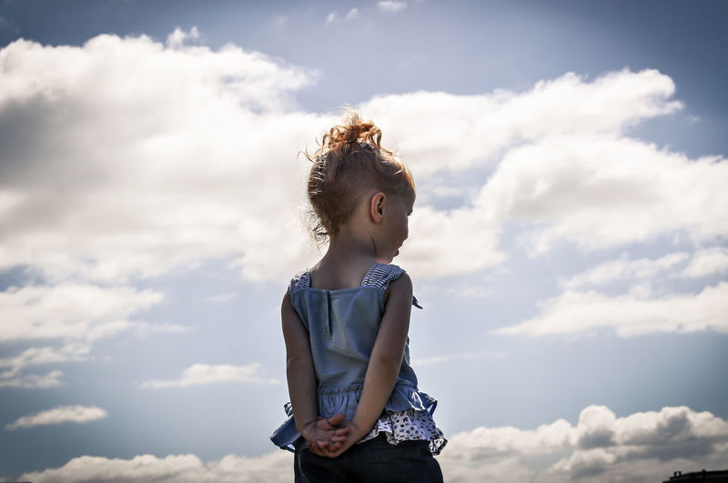 Girl standing against sky