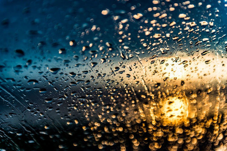 full frame shot of raindrops on glass window Abstract Backgrounds Beauty In Nature Close-up Day Drop Full Frame Glass - Material Nature No People Outdoors Rain RainDrop Sky Sunrise Transparent Water Wet Window