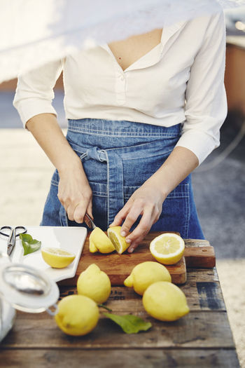 Midsection of woman standing on cutting board