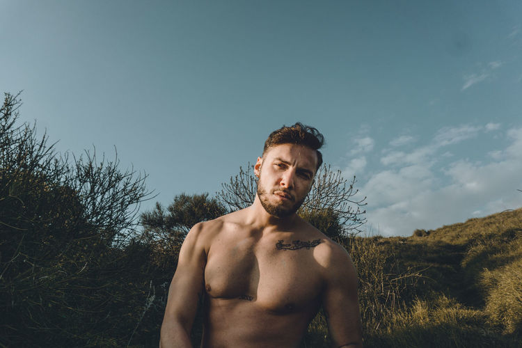 Portrait of shirtless young man standing on land against sky