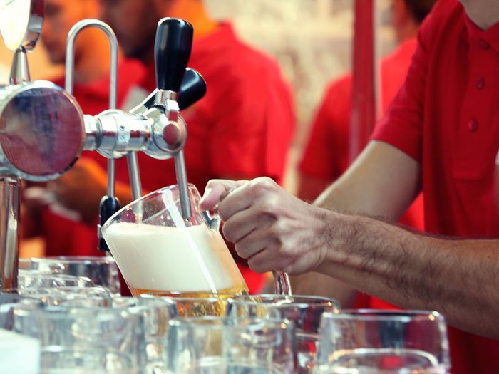 Midsection of man filling glass from beer tap in restaurant