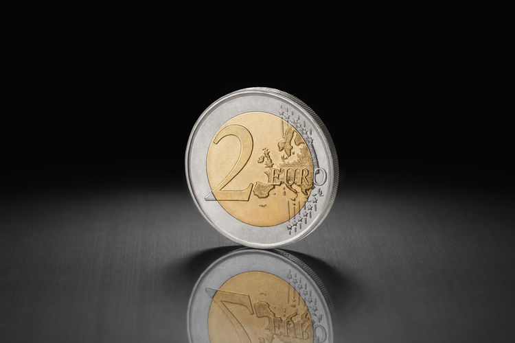 Two euro coin on its side. Macro shot. 2 Euro Coin 2 Euro Coins Black Background High Resolution Reflection Close-up Coin Coin On It's Side Coins On The Table Coins Worldwide Dark Background Euro Europe Macro Metal Surface Money Spotlight Two Euros Coin