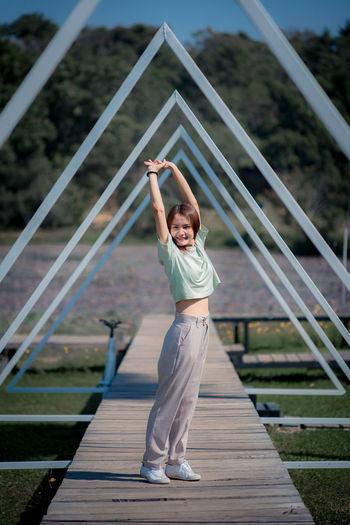 Portrait of girl standing on footbridge