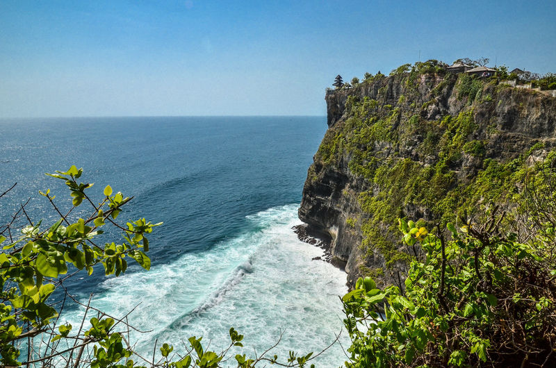 Uluwatu temple on cliff by sea against clear sky