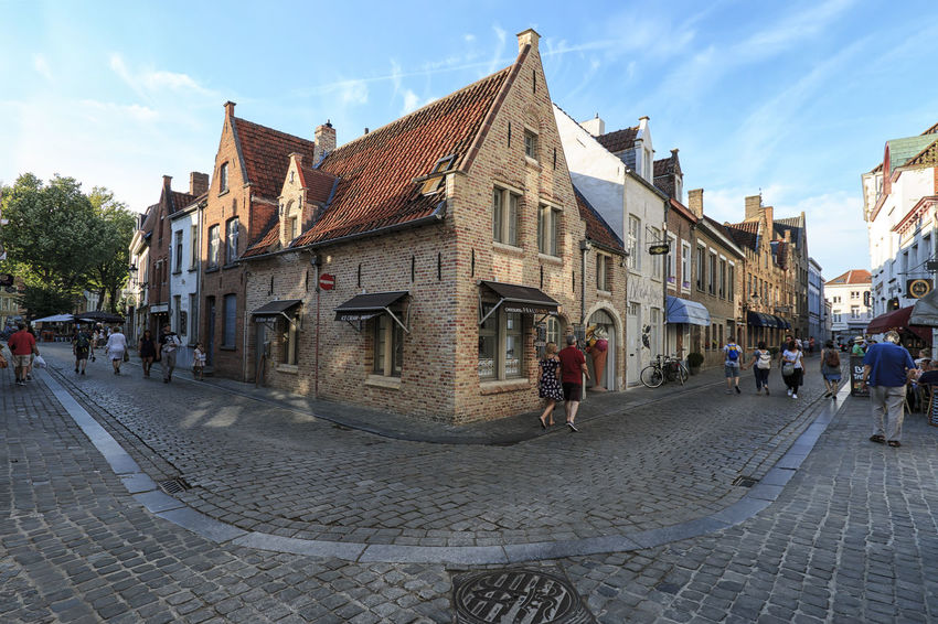 Bruges, Belgium - July 7, 2017: Tourists walking in a old street of Bruges, a medieval town of Belgium Beer Belgium Brugge Chocolate Dijver Canal Duvel Flanders Panoramic View Provinciaal Hof West Flanders Aerial View Belfry Tower Bikes Bruges Europe Flower French Fries Holland Market Square Medieval Town Mussels