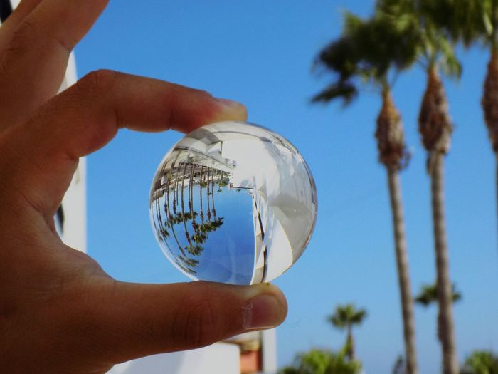 Low angle view of person holding crystal ball against sky