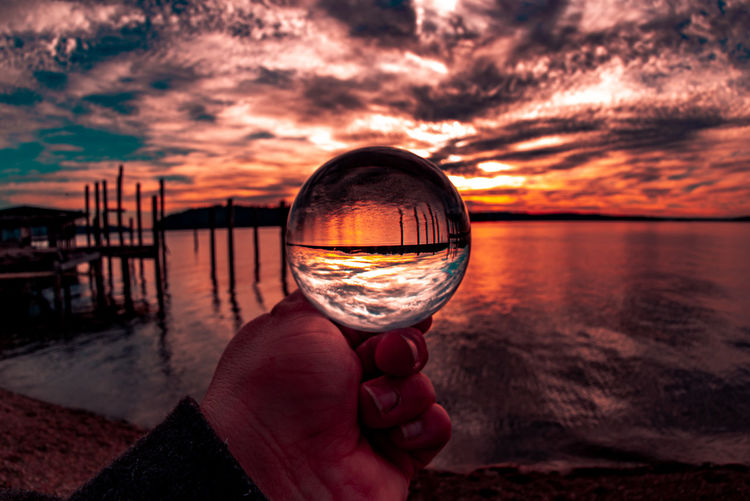 Person holding glass against sea during sunset