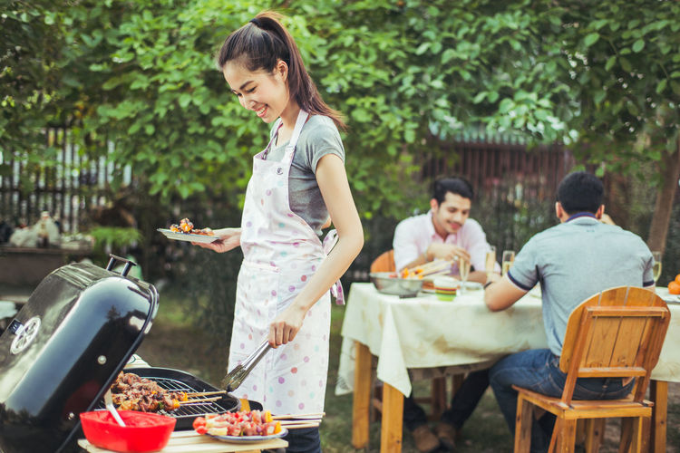 Adult Barbecue Barbecue Grill Casual Clothing Food Food And Drink Friendship Front Or Back Yard Grilled Group Of People Happiness Leisure Activity Lifestyles Men Preparation  Preparing Food Smiling Table Togetherness Women Young Adult Young Men Young Women