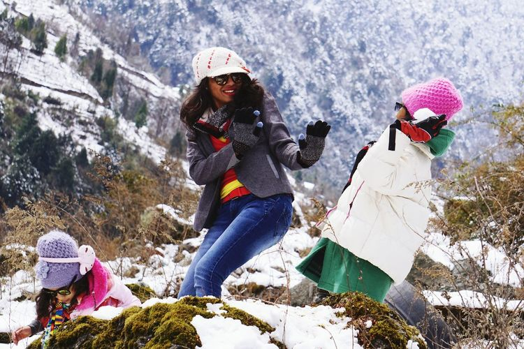 Mother And Daughters Playing With Snow Against Mountains