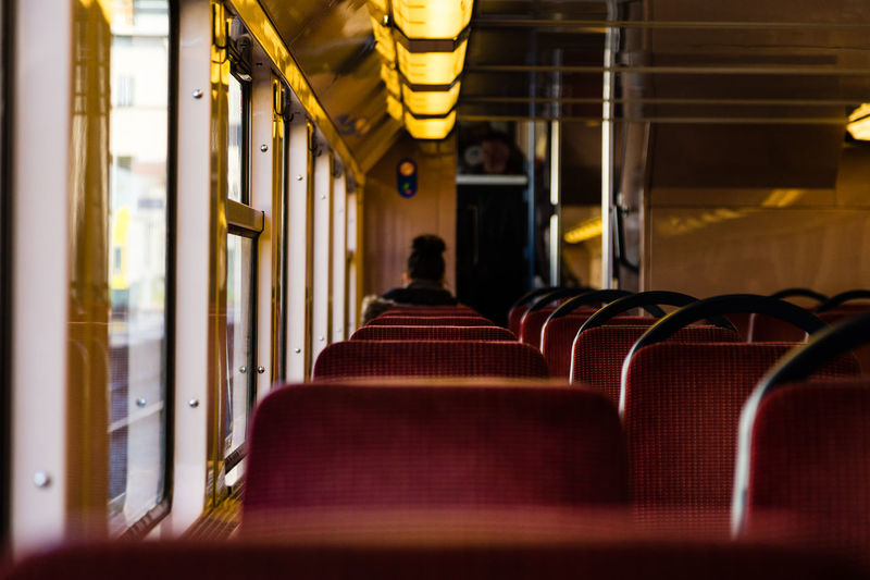 Transportation Adult Aisle Chair Empty Illuminated In A Row Indoors  Luxury Mode Of Transportation One Person Public Transportation Real People Rear View Seat Sitting Train Transportation Travel Vehicle Interior Vehicle Seat Women