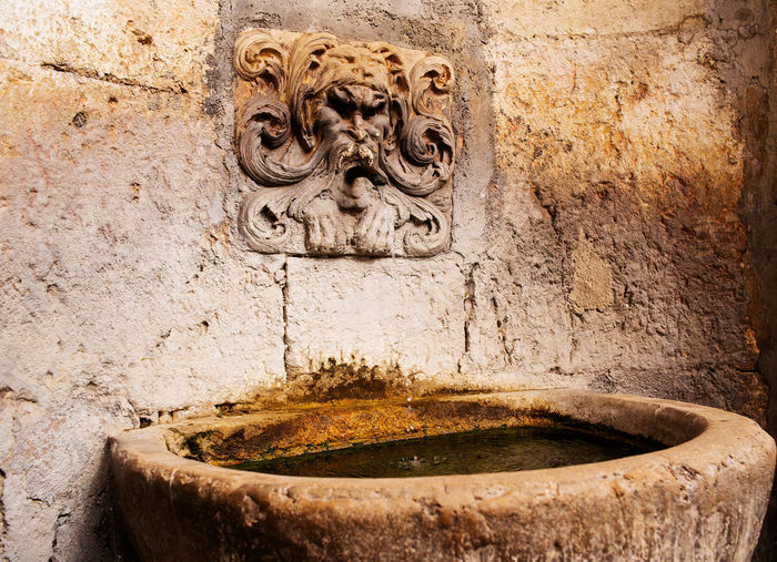 Close-up of old fountain against wall