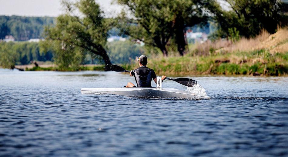 Rear view of man kayaking on lake