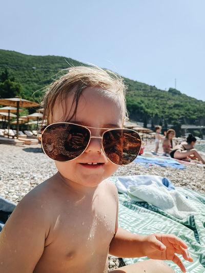 Portrait of shirtless wearing sunglasses on beach
