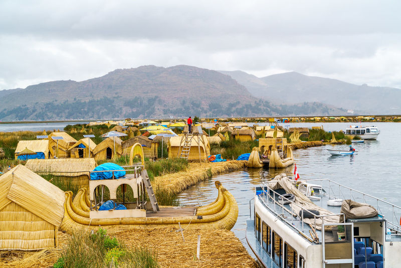 View at the Floating Island Los Uros with typical boats in Lake Titicaca, Puno, Peru Floating Islands Houses Inca Native Culture Plants Puno, Perú Scenic Titicaca Lake Traditional Culture Transportation View Views Boats Colorful Famous Place Famous Places Landmark Landscape Los Urros Peruvian Reeds Ships Travel Destination Village