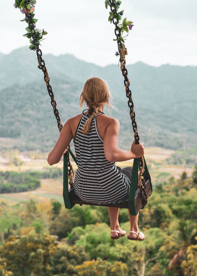 Full length of woman swinging on swing against mountains